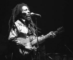 """Robert """"Bob"""" Nesta Marley (n. 6 februarie 1945; d. 11 mai 1981), cântăreț, compozitor, chitarist și activist jamaican. El este cel mai cunoscut interpret de muzică reggae, și este privit ca un profet al mișcării Rastafari - foto (Bob Marley în concert, Zürich, 1980): ro.wikipedia.org"""