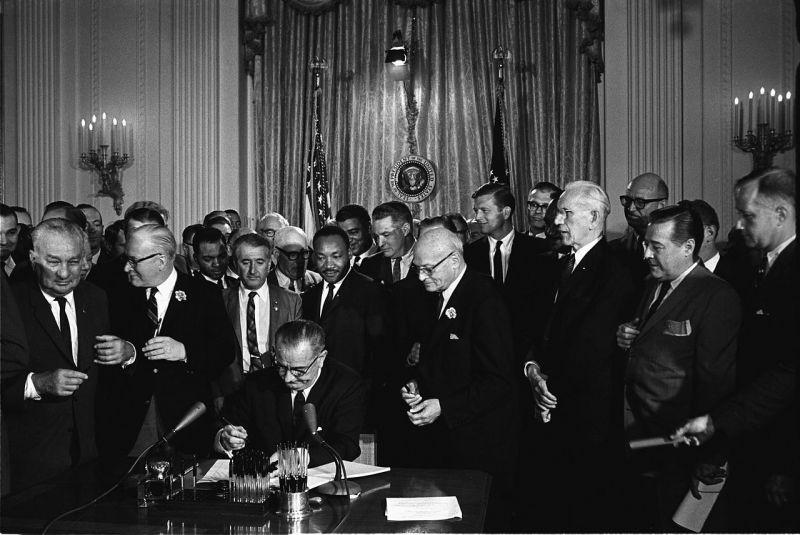 Lyndon B. Johnson promulgă legea drepturilor civile din 1964. Printre invitații aflați în spatele său se numără și Martin Luther King, Jr. - foto preluat de pe ro.wikipedia.org