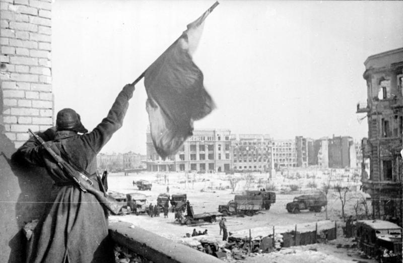 Bătălia de la Stalingrad (21 august 1942 – 2 februarie 1943) a reprezentat un important punct de cotitură în desfăşurarea celui de-al Doilea Război Mondial şi este considerată cea mai sângeroasă şi mai mare bătălie din istoria omenirii - in imagine, Soldat sovietic fluturând steagul roșu în piață centrală de la Stalingrad, 1943 - foto: ro.wikipedia.org