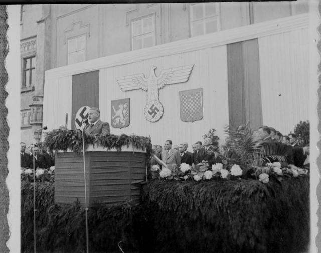 """Jaroslav Krejčí, cancelar al Protectoratului, în timpul unui miting din Tábor. Peretele din spatele tribunei este decorat cu steagurile Reichului, ale Protectoratului și cu vulturul nazist cu aripile deschise """"protectoare"""" deasupra leului Boemiei și vulturului Maraviei - foto: ro.wikipedia.org"""