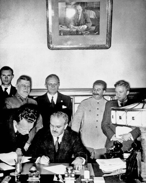 Ministrul sovietic de externe Viaceslav Molotov semnând Pactul de neagresiune sovieto-german. În spatele său se văd ministrul de externe german Joachim von Ribbentrop (stânga) și primul ministru sovietic Iosif Vissarionovici Stalin. - foto preluat de pe istoria.md