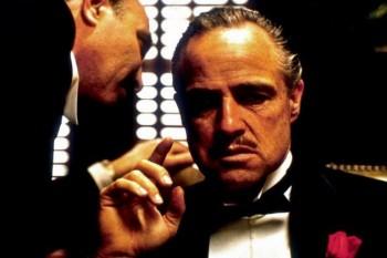 """Marlon Brando, Jr. (n. 3 aprilie 1924 – d. 1 iulie 2004) a fost un actor american câștigător al premiului Oscar, recunoscut ca fiind unul dintre cei mai mari actori de film ai secolului 20. S-a făcut remarcat mai ales datorită rolurilor din filmele """"Un tramvai numit dorință"""" și """"On the Waterfront"""", ambele regizate de către Elia Kazan la începutul anilor 1950. Stilul său actoricesc, combinat cu aparițiile sale publice ca outsider al Hollywood-ului anilor 1950 și 1960, au avut o influență majoră asupra generației de actori ce i-au urmat - in imagine, Marlon Brando în """"Nașul"""""""