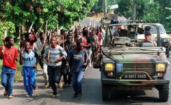 In aceasta fotografie, facuta in 27 iunie 1994, soldatii francezi trec pe langa luptatorii etnici hutu ai fortelor guvernamentale din Rwanda, in apropiere de Gisenyie, aproximativ 10 km de granita cu Zairul. Soldatii si militiile hutu au ucis aproape un milion de etnici tutsi. (Pascal Guyot / AFP / Getty Images) - foto preluat de pe epochtimes-romania.com