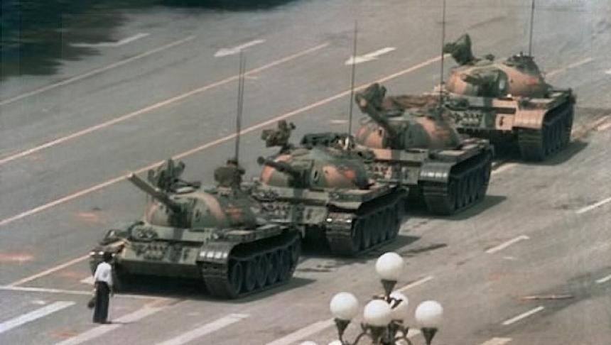 """""""Omul din Piața Tiananmen"""" oprește temporar înaintarea unei coloane de tancuri la data de 5 iunie 1989, la Beijing, în ceea ce este considerat una dintre cele mai reprezentative imagini ale secolului XX. Această fotografie (una din cele patru versiuni similare) a fost realizată de Jeff Widener de la Associated Press - foto preluat de pe historia.ro"""