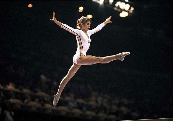 """Nadia Elena Comăneci (n. 12 noiembrie 1961, Onești, județul Bacău) este o gimnastă română, prima gimnastă din lume care a primit nota zece într-un concurs olimpic de gimnastică. Este câștigătoare a cinci medalii olimpice de aur. Este considerată a fi una dintre cele mai bune sportive ale secolului XX și una dintre cele mai bune gimnaste ale lumii, din toate timpurile, """"Zeița de la Montreal"""", prima gimnastă a epocii moderne care a luat 10 absolut. Este primul sportiv român inclus în memorialul International Gymnastics Hall of Fame - foto: pinterest.com"""