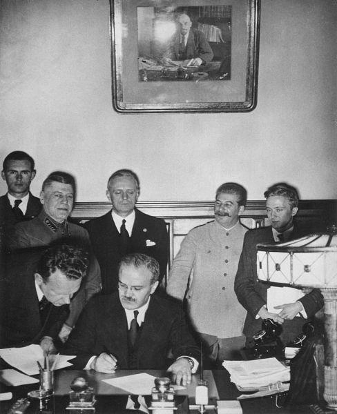 Ministrul sovietic de externe Viaceslav Molotov semnând Pactul de neagresiune sovieto-german. În spatele său se văd ministrul de externe german Joachim von Ribbentrop (stânga) și primul ministru sovietic Iosif Vissarionovici Stalin (23 august 1939) - foto preluat de pe ro.wikipedia.org