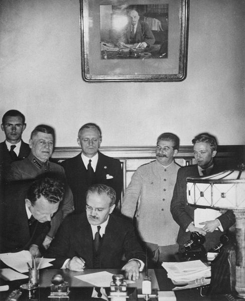 Ministrul sovietic de externe Viaceslav Molotov semnând Pactul de neagresiune sovieto-german. În spatele său se văd ministrul de externe german Joachim von Ribbentrop (stânga) și primul ministru sovietic Iosif Vissarionovici Stalin - foto: ro.wikipedia.org