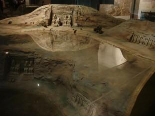 1968: Se finalizează transferul celor două temple de la Abu Simbel pentru salvarea acestora de apele lacului Nasser. Între 1964 și 1968, tot site-ul a fost atent tăiat în blocuri mari, demontate, ridicate și reasamblate într-un nou loc, cu 65 de metri mai mare și la 200 de metri mai sus de râu, într-una dintre cele mai mari provocările de inginerie arheologică din istorie. Un model la scară indică locația originală și actuală a templului - foto: ro.wikipedia.org