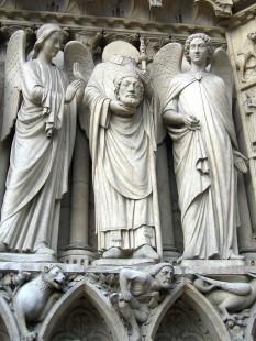 Sfântul Dionisie, conform tradiției, primul episcop de Paris. Este considerat unul din cei 14 sfinți ajutători, reprezentat ca ținându-și în mână propriul cap, cu referire la martiriul său în secolul al III-lea - foto (Sfântul Dionisie între doi îngeri, portalul Fecioarei Maria, Catedrala Notre Dame de Paris): ro.wikipedia.org