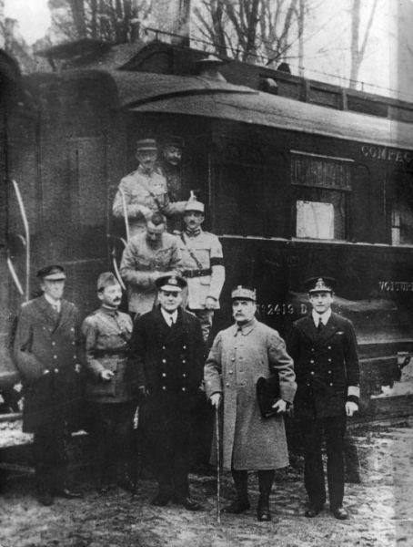 Fotografie realizată la semnarea armistiţiului, în faţa vagonului de tren al mareşalului Foch, în pădurea Compiègne. Mareşalul Ferdinand Foch este al doilea din dreapta foto preluat de pe ro.wikipedia.org