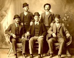 Robert LeRoy Parker, cunoscut sub numele de Butch Cassidy, jos, in partea dreaptă a fotografiei, cu mâna așezată pe brațul scaunului. Sundance Kid (Harry Alonzo Longabaugh), este așezat pe extrema stângă a imaginii foto: cersipamantromanesc.wordpress.com