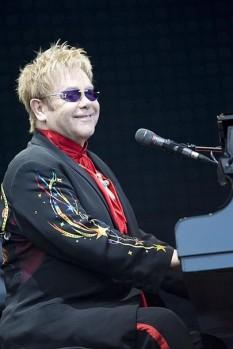 Sir Elton Hercules John (n. Reginald Kenneth Dwight, pe 25 martie 1947), cunoscut sub numele de scenă Elton John, cântăreț, compozitor, cantautor și pianist englez. A lucrat cu partenerul său muzical Bernie Taupin din 1967; până în prezent au colaborat la peste 30 de albume -  foto (Elton John în timpul unui concert din 2008): ro.wikipedia.org