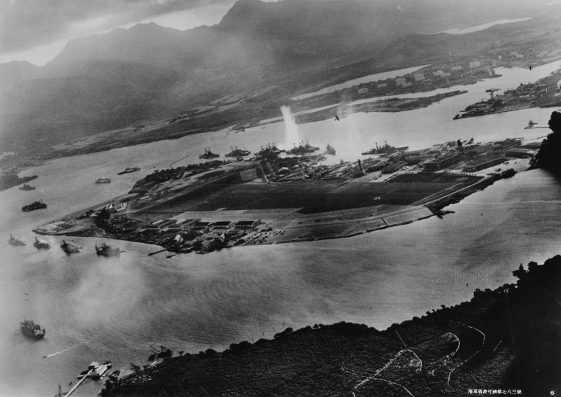 Photograph of Battleship Row taken from a Japanese plane at the beginning of the attack. The explosion in the center is a torpedo strike on USS West Virginia. Two attacking Japanese planes can be seen: one over USS Neosho and one over the Naval Yard - foto: en.wikipedia.org