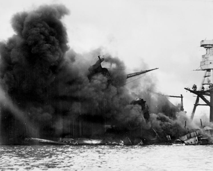 The USS Arizona (BB-39) burning after the Japanese attack on Pearl Harbor, 7 December 1941. The ship is resting level on the bottom. The supporting structure for the gun director tripod mast has collapsed and so the mast has tilted - foto: ro.wikipedia.org