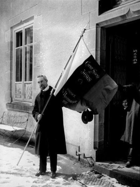 Monseniorul Vladimir Ghika (n. 25 decembrie 1873, Istanbul (vechiul Constantinopol), Imperiul Otoman - d. 16 mai 1954, Jilava, Bucureşti) a fost un prinţ, diplomat, scriitor, om de caritate, preot catolic român (biritual: latin şi bizantin), nepotul lui Grigore Alexandru Ghica, ultimul principe al Moldovei. Tatăl lui Vladimir Ghika a fost Ioan Grigore Ghica, diplomat, ministru de externe si al apărării al României. Unul dintre fraţii monseniorului a fost Dimitrie I. Ghica. Monseniorul Vladimir Ghika a fost beatificat pe data de 31 august 2013, la Bucureşti, în cadrul unei slujbe religioase solemne desfăşurată la pavilionul Rom-Expo - in imagine, Vladimir Ghika poartă drapelul cu ecusonul Preasfintei Inimi a lui Isus din România, Paray-le-Monial, Saône-et-Loire, Franţa (27 martie 1917) - foto: ro.wikipedia.org