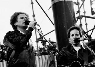 """Simon & Garfunkel este un duo american de cantautori format din Paul Simon și Art Garfunkel. Ei au format trupa Tom & Jerry în 1957 și au cunoscut pentru prima dată succesul odată cu minihitul """"Hey, Schoolgirl"""". Sub numele Simon & Garfunkel, duo-ul a devenit celebru în 1965 când au lansat hit single-ul """"The Sounds of Silence"""". Mai mult, muzica lor s-a regăsit și pe coloana sonoră a filmului Absolventul, ceea ce i-a propulsat și mai mult în conșțiința publicului - in imagine, Simon & Garfunkel performing in Dublin, 1982 - foto: ro.wikipedia.org"""