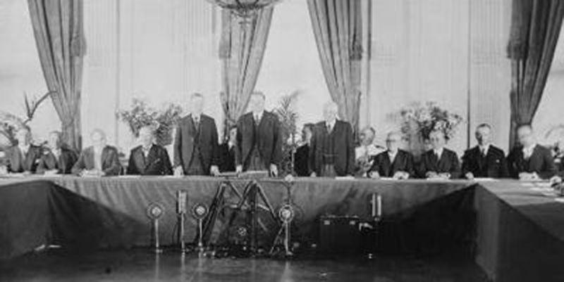 """Pactul Kellogg-Briand (27 august 1928): Calvin Coolidge, Herbert Hoover și Frank B. Kellogg, (în picioare), alături de reprezentanții guvernelor care au ratificat """"Tratatul pentru renunțare la război"""" (Pactul Kellogg-Briand), în """"Camera de răsărit"""" a Casei Albe - foto preluat de pe ro.wikipedia.org"""