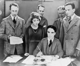 5 februarie 1919 – A fost creată compania United Artists (UA), unele dintre cele mai mari studiouri cinematografice ale secolului trecut de către Charlie Chaplin, Mary Pickford, Douglas Fairbanks şi D.W. Griffith, in imagine, D.W. Griffith, Mary Pickford, Charlie Chaplin (aşezat) şi Douglas Fairbanks, la semnarea contractului de instituire United Artists. În spate avocaţii Albert Banzhaf (stânga) şi Dennis F. O'Brien (dreapta) - foto: ro.wikipedia.org