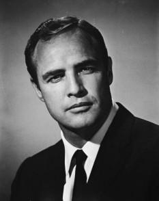 """Marlon Brando, Jr. (n. 3 aprilie 1924 – d. 1 iulie 2004) a fost un actor american câștigător al premiului Oscar, recunoscut ca fiind unul dintre cei mai mari actori de film ai secolului 20. S-a făcut remarcat mai ales datorită rolurilor din filmele """"Un tramvai numit dorință"""" și """"On the Waterfront"""", ambele regizate de către Elia Kazan la începutul anilor 1950. Stilul său actoricesc, combinat cu aparițiile sale publice ca outsider al Hollywood-ului anilor 1950 și 1960, au avut o influență majoră asupra generației de actori ce i-au urmat - foto: biography.com"""
