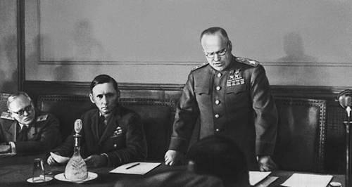 Actul capitulării Germaniei (07 - 08 mai 1945) - Mareșalul Uniunii Sovietice Gheorghi Jukov citind actul capitulării Germaniei la Cartierul său General din Berlin. La dreapta sa se află Mareșalul Forțelor Aeriene al Regatului Unit, Arthur Tedder - foto preluat de pe ro.wikipedia.org