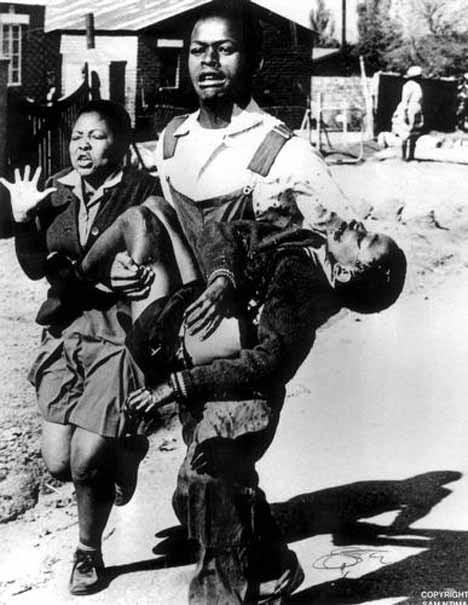 Hector Pieterson purtat pe brate de Mbuyisa Makhubo după ce a fost împușcat de poliția din Africa de Sud. Sunt insotiti de sora lui, Antoaneta Sithole. Pieterson a fost dus de urgenta la o clinica locala si declarat mort la sosire - foto:google.com