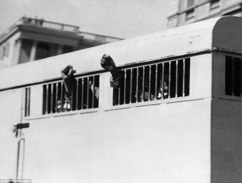 This picture taken on June 16, 1964 shows eight men, among them anti-apartheid leader and African National Congress (ANC) member Nelson Mandela, sentenced to life imprisonment in the Rivonia trial leaving the Palace of Justice in Pretoria with their fists raised in defiance through the barred windows of the prison car - foto: dailymail.co.uk