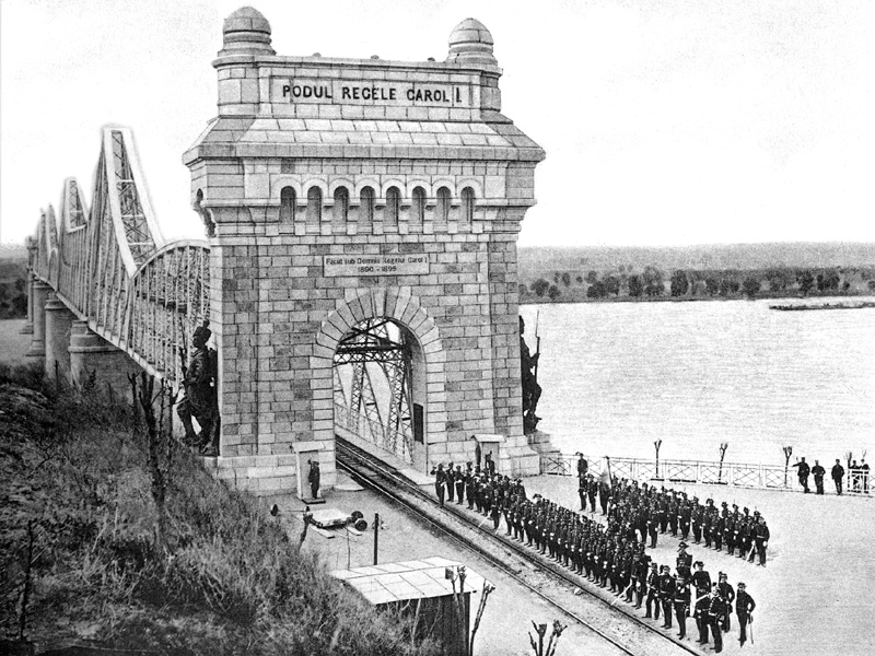"""Podul Regele Carol I (redenumit mai apoi Podul Anghel Saligny, pentru a-l onora pe Anghel Saligny proiectantul și executantul podului) a fost construit între 1890 și 1895 pentru a asigura legătura feroviară între București și Constanța. Podul este înscris în Lista Monumentelor Istorice sub denumirea Podul Carol I cu statuile """"Dorobanții"""" - foto: ro.wikipedia.org"""