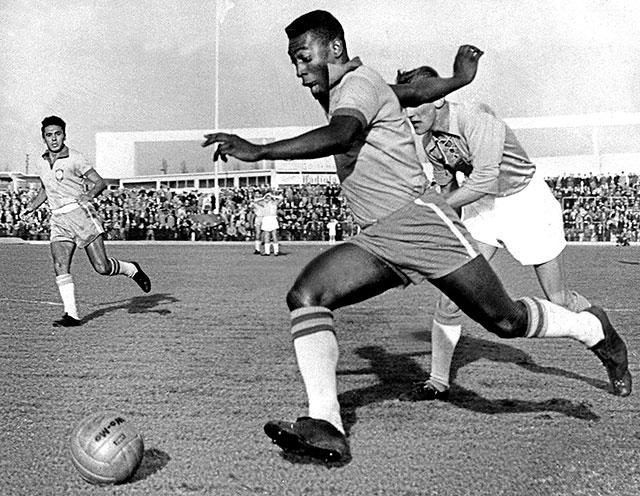 Edson Arantes do Nascimento (n. 23 octombrie 1940) este un fotbalist profesionist brazilian retras, care este considerat a fi cel mai mare jucător din toate timpurile - in imagine, Pelé dribbling past a defender while playing for Brazil, May 1960. - foto preluat de pe en.wikipedia.org
