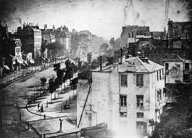 """Boulevard du Temple"", taken by Daguerre in 1838 in Paris, includes the earliest known candid photograph of a person. The image shows a busy street, but because the exposure had to continue for several minutes the moving traffic is not visible. At the lower left, however, a man apparently having his boots polished, and the bootblack polishing them, were motionless enough for their images to be captured - foto preluat de pe en.wikipedia.org"