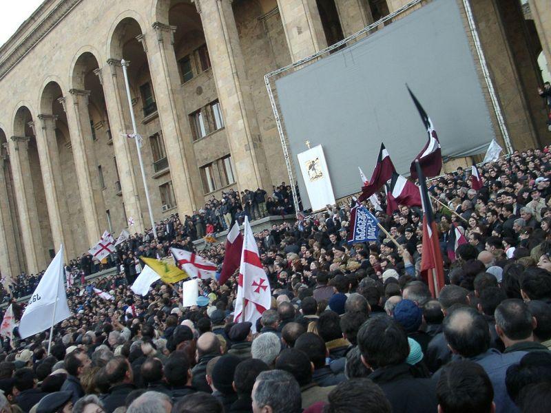 Revoluția Trandafirilor (3 - 23 noiembrie 2003) a fost o schimbare a puterii politice în Georgia în noiembrie 2003, care a avut loc după proteste în masă ca urmare a alegerilor parlamentare contestate. Ulterior, președintele Eduard Șevardnadze a fost forțat să demisioneze la data de 23 noiembrie 2003 (Proteste lângă sediul Parlamentului, în ziua demisiei lui Șevardnadze) - foto preluat de pe ro.wikipedia.org
