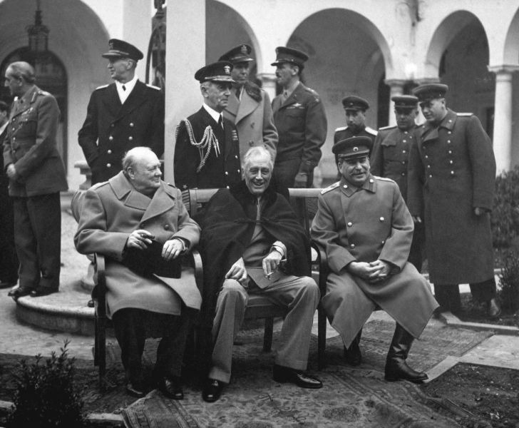 "Conferința de la Ialta (4 - 11 februarie 1945) - The ""Big Three"" at the Yalta Conference, Winston Churchill, Franklin D. Roosevelt and Joseph Stalin. Behind them stand, from the left, Field Marshal Sir Alan Brooke, Fleet Admiral Ernest King, Fleet Admiral William D. Leahy, General of the Army George Marshall, Major General Laurence S. Kuter, General Aleksei Antonov, Vice Admiral Stepan Kucherov, and Admiral of the Fleet Nikolay Kuznetsov - foto preluat de pe ro.wikipedia.org"