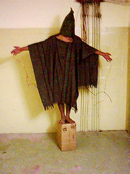 """This image of a prisoner, Ali Shallal al-Qaisi, being tortured has become internationally famous, eventually making it onto the cover of The Economist (see """"Media Coverage"""" below) - foto preluat de pe en.wikipedia.org"""
