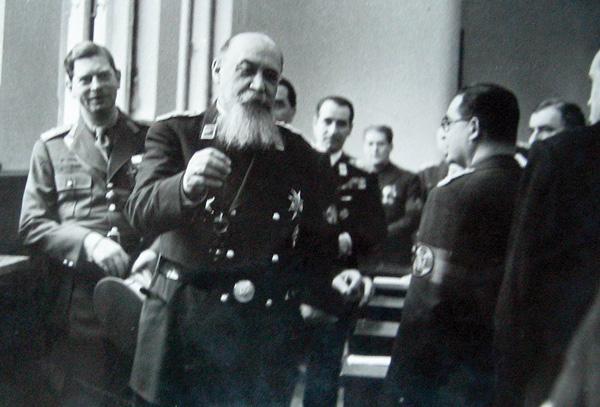 Nicolae Iorga în uniforma militară a partidului unic Frontul Renașterii Naționale. În fundal stânga, regele Carol al II-lea. În dreapta, din profil, Armand Călinescu - foto preluat de pe ro.wikipedia.org