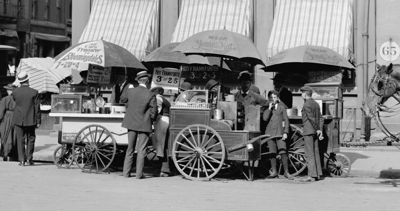 "Carts selling frankfurters in New York City, circa 1906. The price is listed as ""3 cents each or 2 for 5 cents"" - foto preluat de pe en.wikipedia.org"