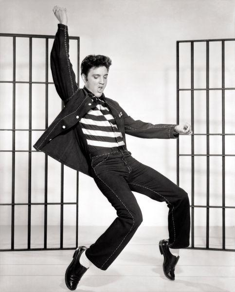 Elvis Aaron Presley (n. 8 ianuarie 1935, Tupelo, Mississippi - d. 16 august 1977, Memphis, Tennessee) a fost un cântăreț și actor american, cunoscut frecvent ca Regele Rock 'n' Roll-ului sau simplu, The King, cu toate ca a obținut și trei premii Grammy pentru muzică Gospel. - (Elvis Presley in a publicity photograph for the 1957 film Jailhouse Rock) - foto preluat de pe en.wikipedia.org