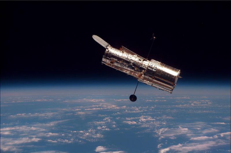 Telescopul Spațial Hubble  văzut de pe naveta spațială Discovery  în timpul celei de-a doua misiuni  destinată telescopului STS-82 - foto preluat de pe ro.wikipedia.org